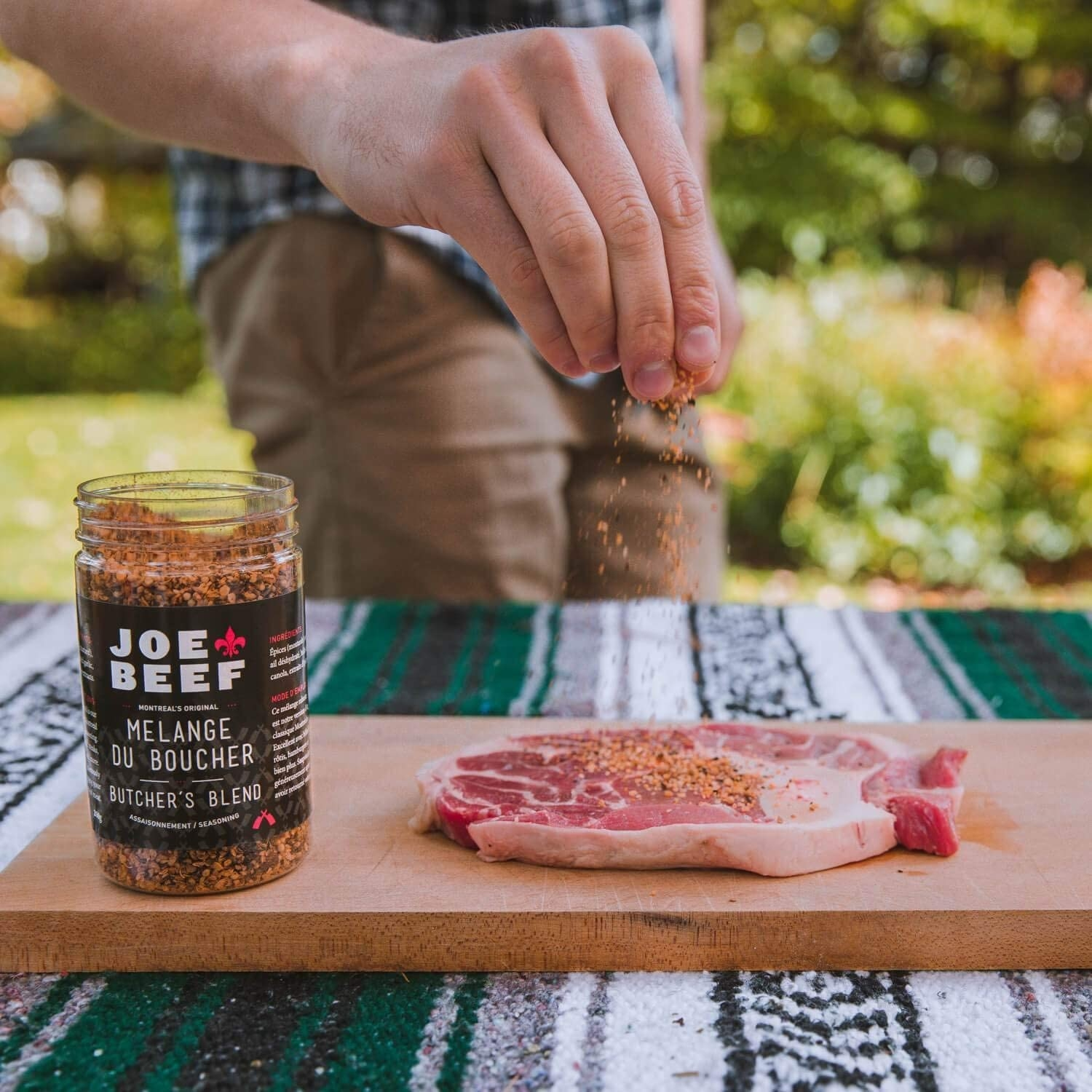 A hand is sprinkling seasoning onto a piece of meat on a cutting board with a bottle of seasoning beside it