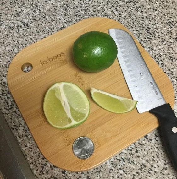 Reviewer's picture of the mini bamboo cutting board being used to cut limes