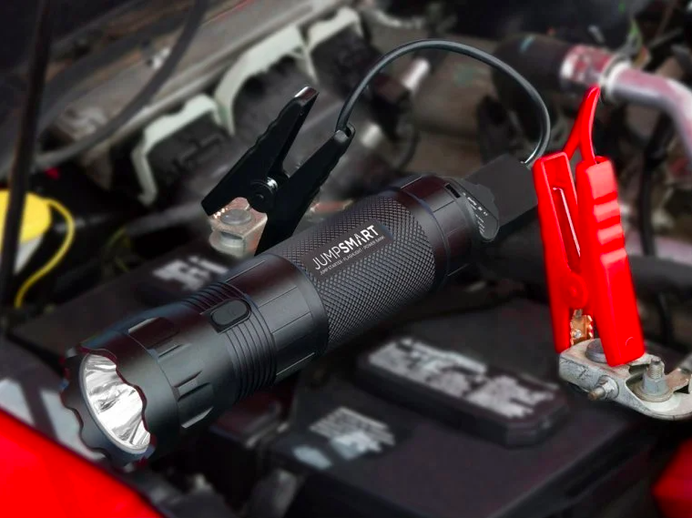 A flashlight-like device and two plugs under the hood of a car
