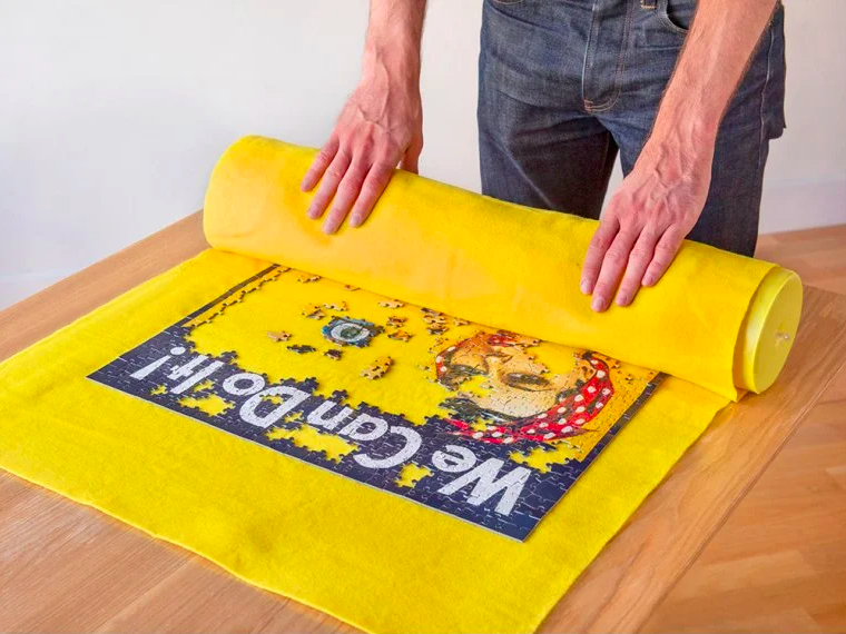 person rolling up a puzzle on a mat that fits around a cylinder
