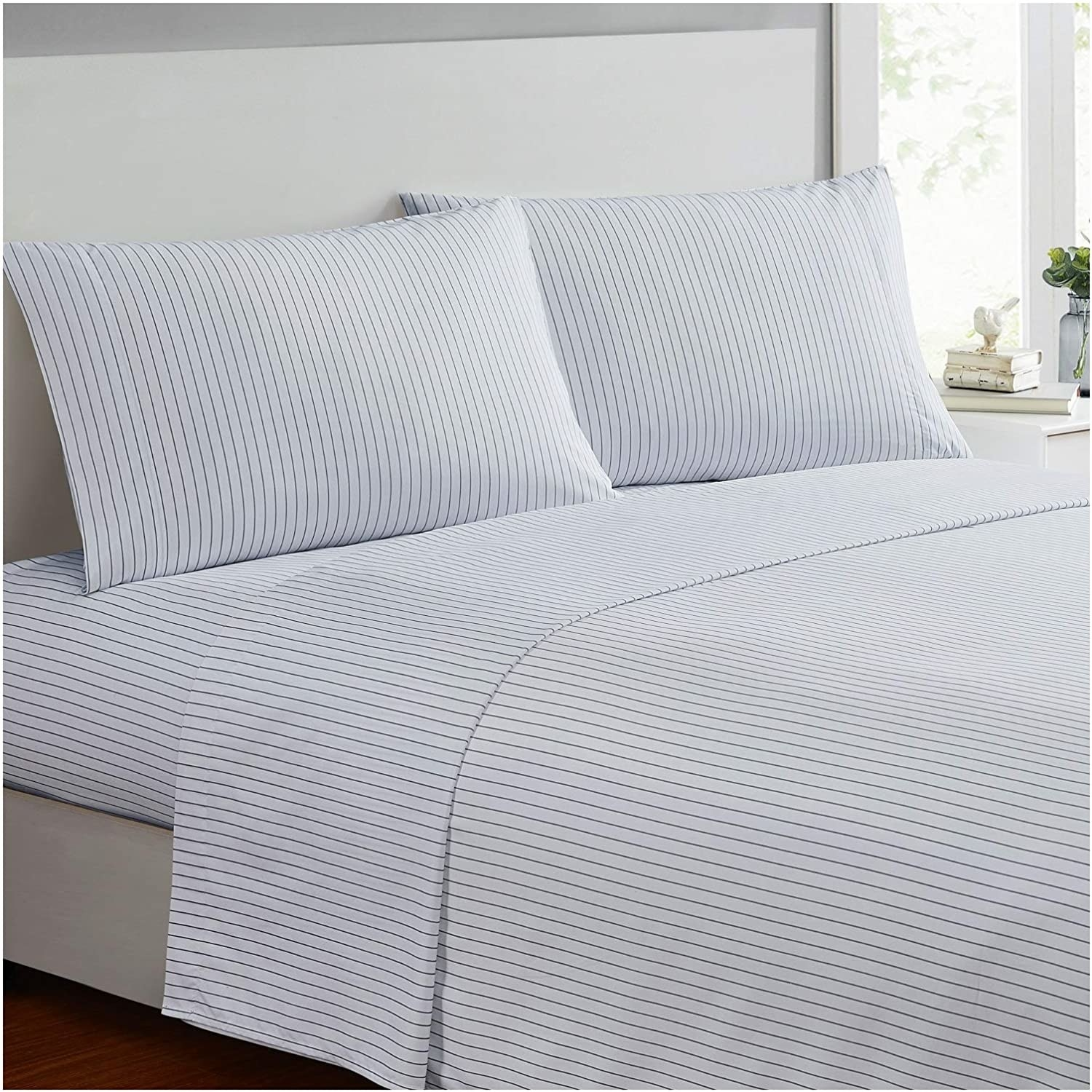a bed showcasing white sheets with thin blue vertical stripes down them and matching pillowcases