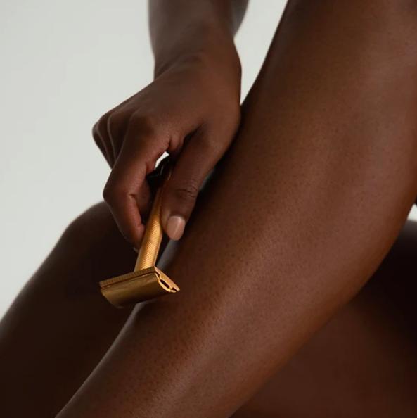 a model holds a matte gold razor to leg
