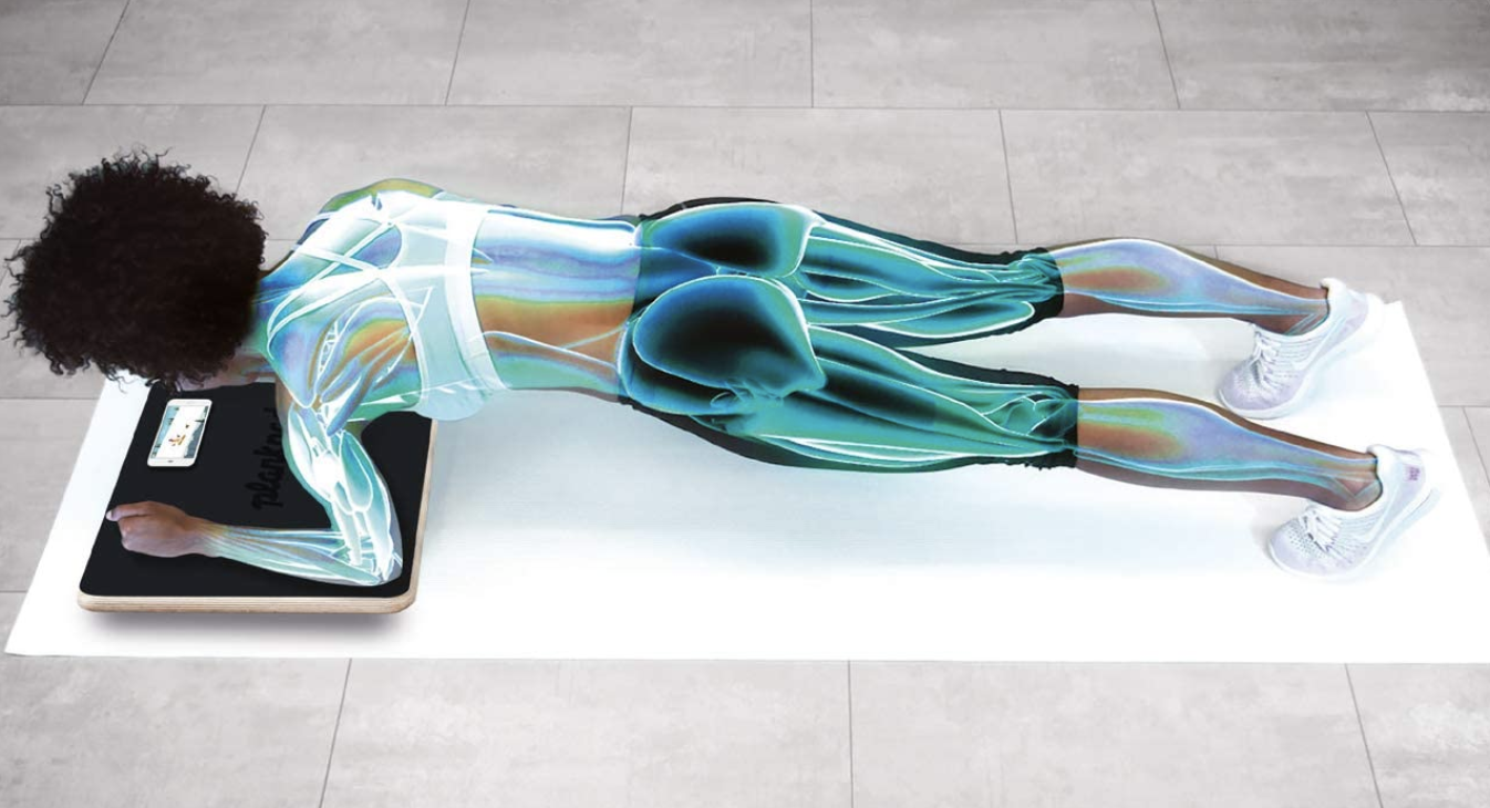 A model uses an interactive Plankboard while working out indoors