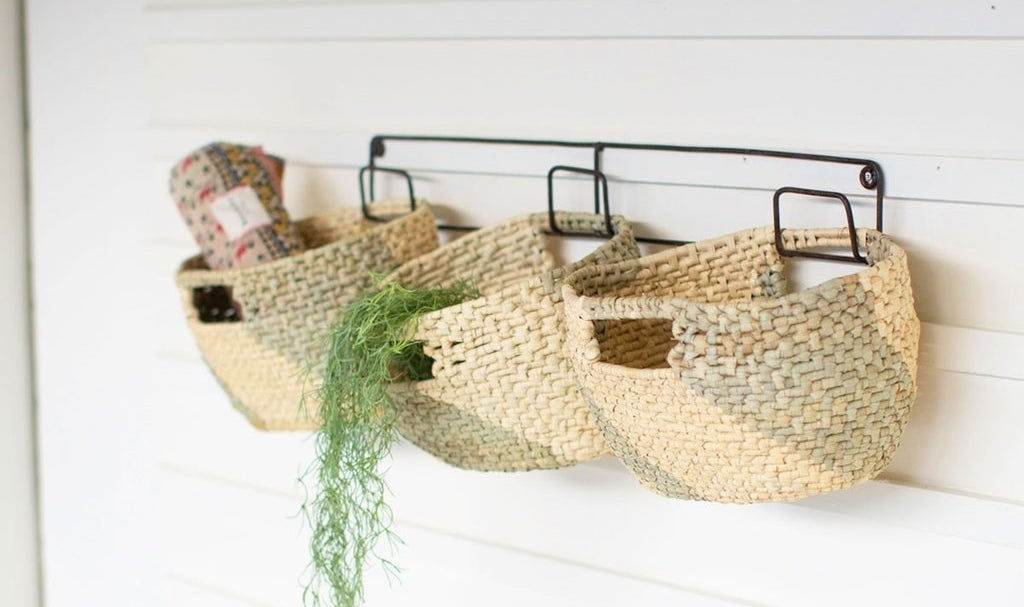 The three woven baskets and the wall frame against a wall