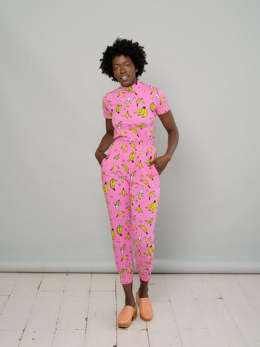 model wears short sleeve jumpsuit covered in bananas