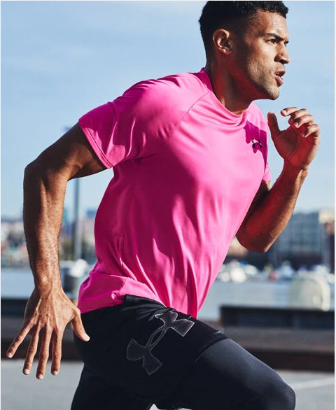 A model wearing a bright pink short-sleeve shirt while running