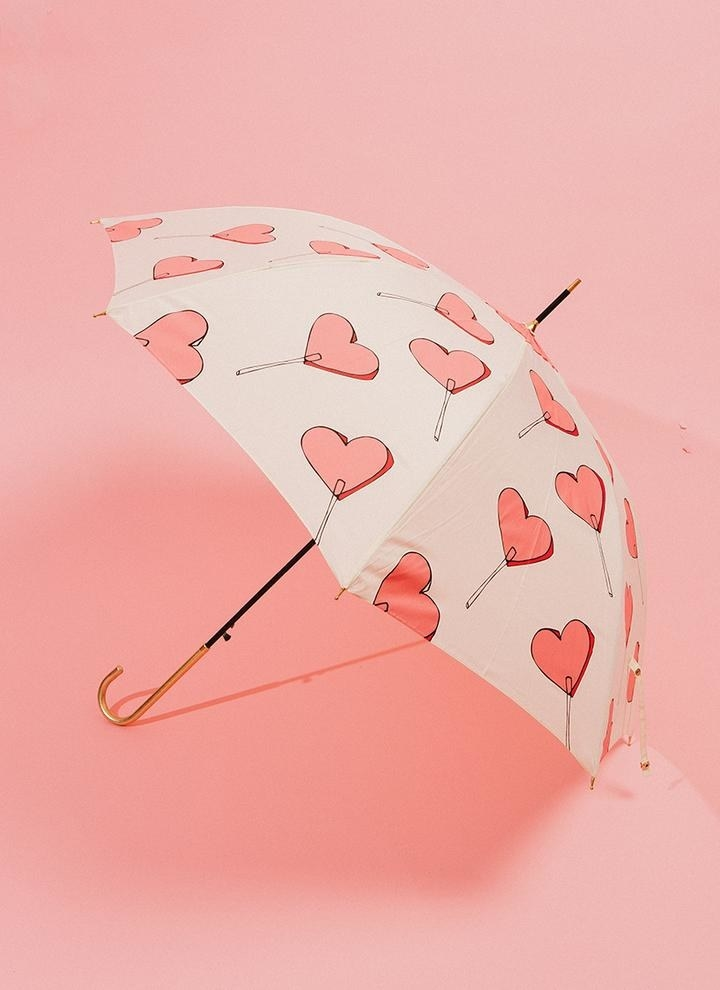 a white umbrella with illustrated pink heart lollipops