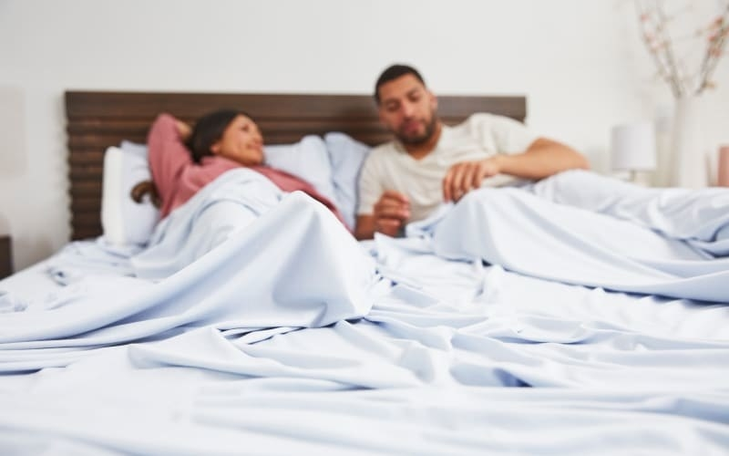 a couple in bed under the stretchy light blue sheets