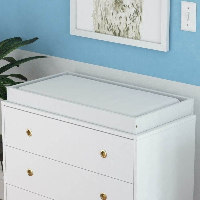 The changing table topper on a dresser