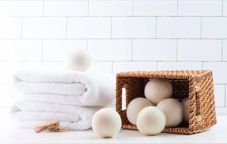 the wool balls with a stack of towels and in a basket