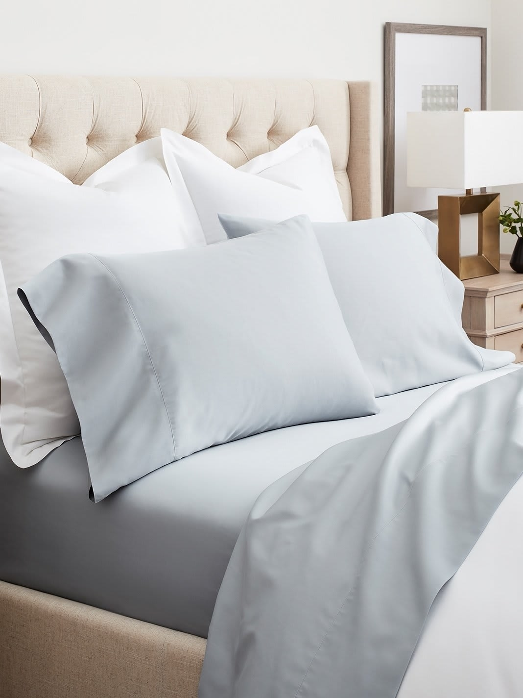 A bed with pale blue sheets and pillowcases