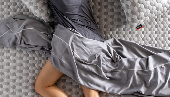 a model laying on their stomach with the grey sheet horizontally over them