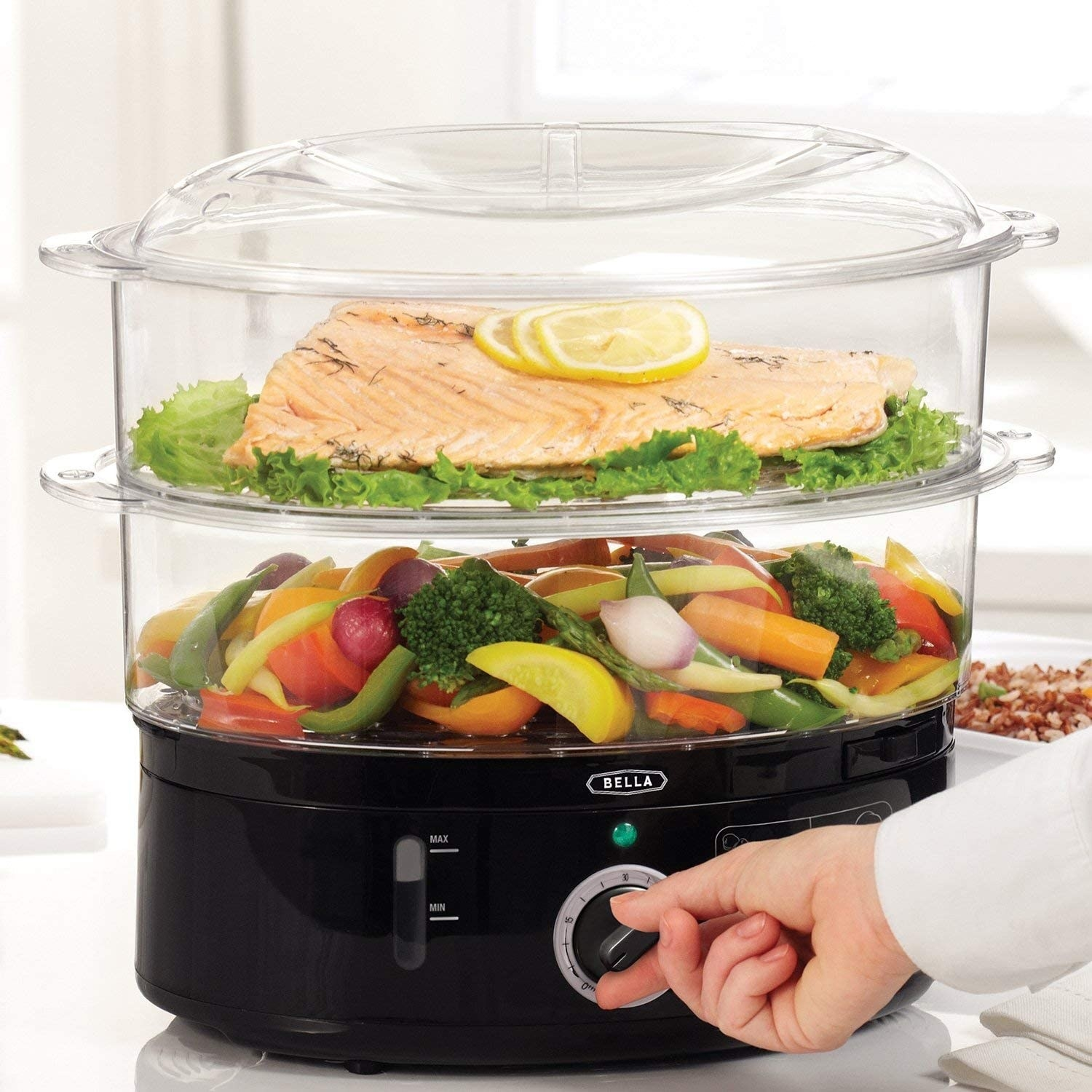 A steam machine has veggies on the bottom layer and salmon on the top