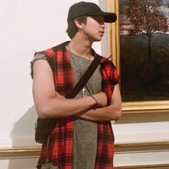 RM looks off to the side while posing in front of an artwork