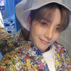 J-Hope smiles for the camera while taking a selfie; he wears a jacket covered in cartoon characters and a white bucket hat