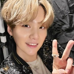 Suga smiles at the camera while doing a peace sign; he has blonde hair
