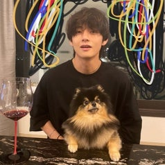 V looks at the camera with his dog, Yeontan, in his lap; they're seated at a table which has a glass of wine on it; there is scribbles drawn on the photo in the background to cover a mirror