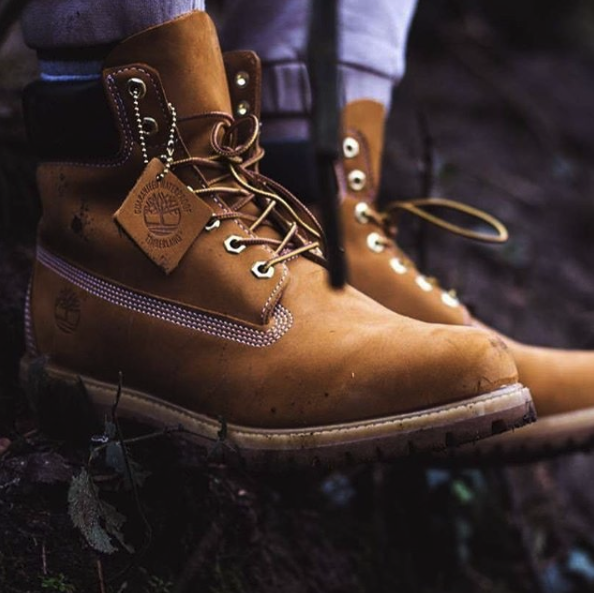Close up of waterproof, leather Timberland boots on feet, on ground outdoors