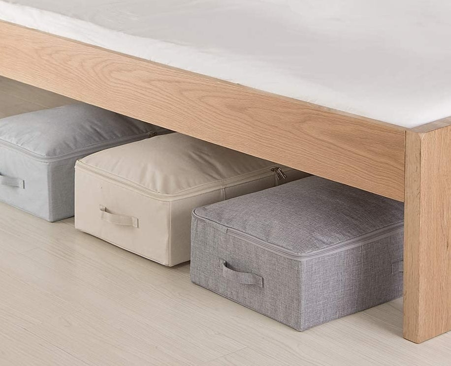 three storage boxes under a bed in grey, nude, and silver