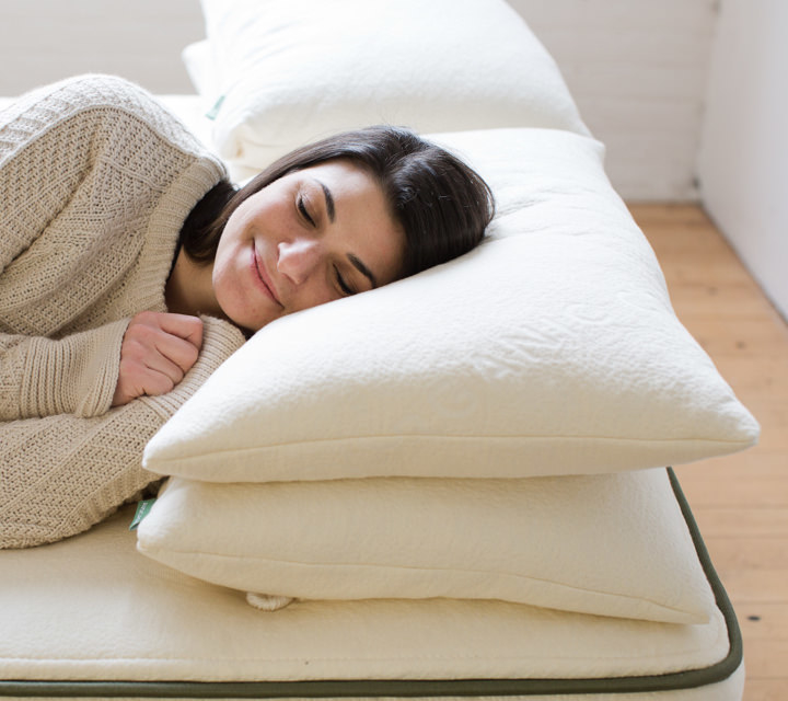 person sleeping on side with two pillows stacked underneath head