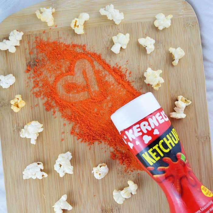 A shaker of ketchup flavouring surrounded by popped kernels of popcorn