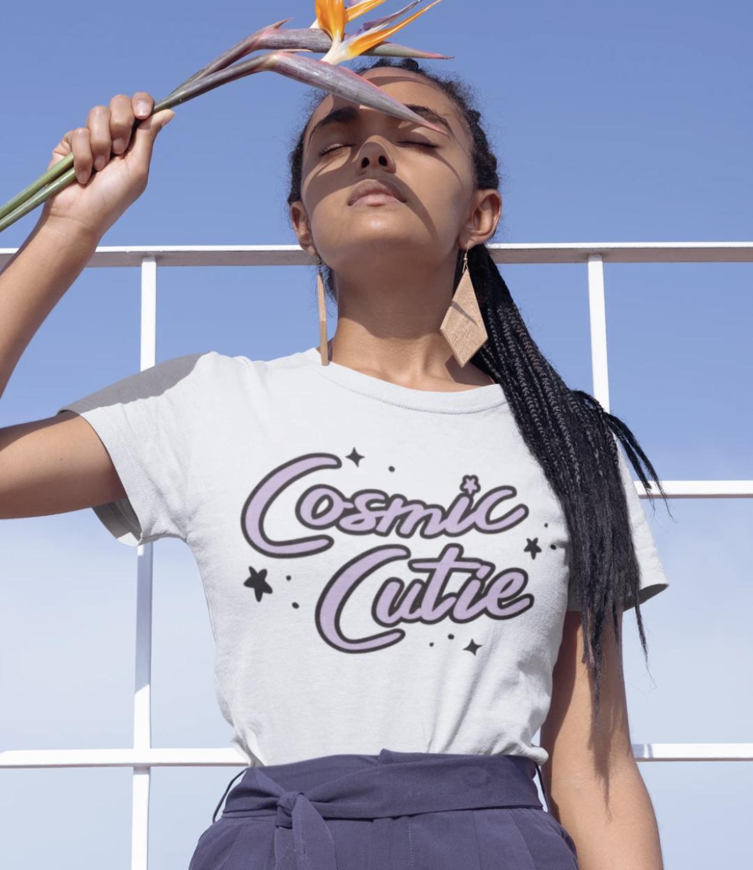"""Model wears white tee that says """"Cosmic Cutie"""" in purple lettering"""