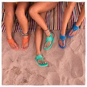 Three models wearing different colored Sanuk sling sandals on the beach