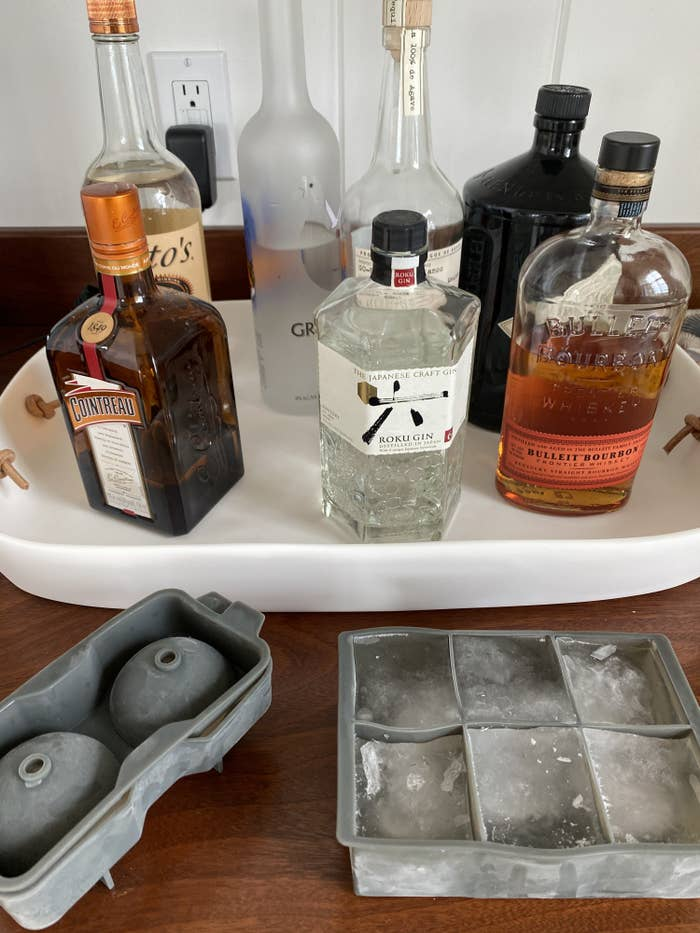 A wet bar with bottles of alcohol and two sets of jumbo ice cube molds-- one spherical and one square.