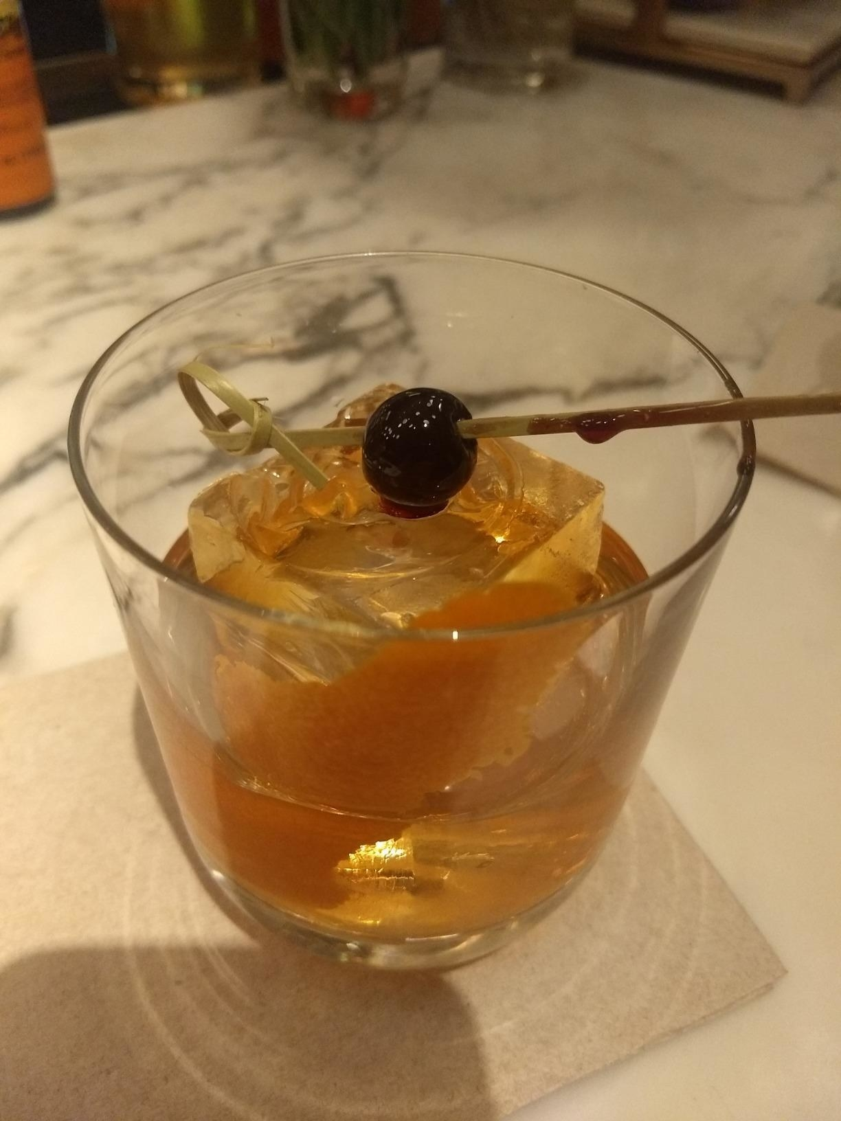 An Old-Fashioned whiskey cocktail with a jumbo ice cube inside of the glass.