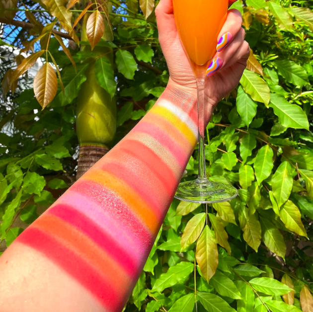 hand holds mimosa and shows arm covered in all the colors from the palettes (mostly pinks and oranges)