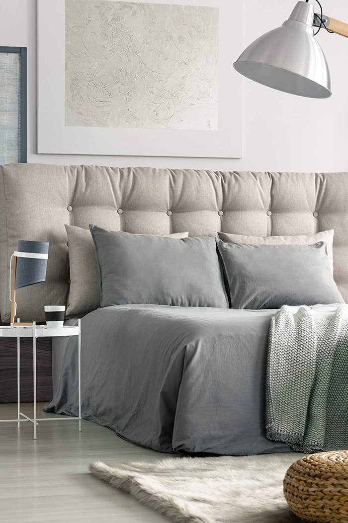 the sheets on the bed and pillows in grey