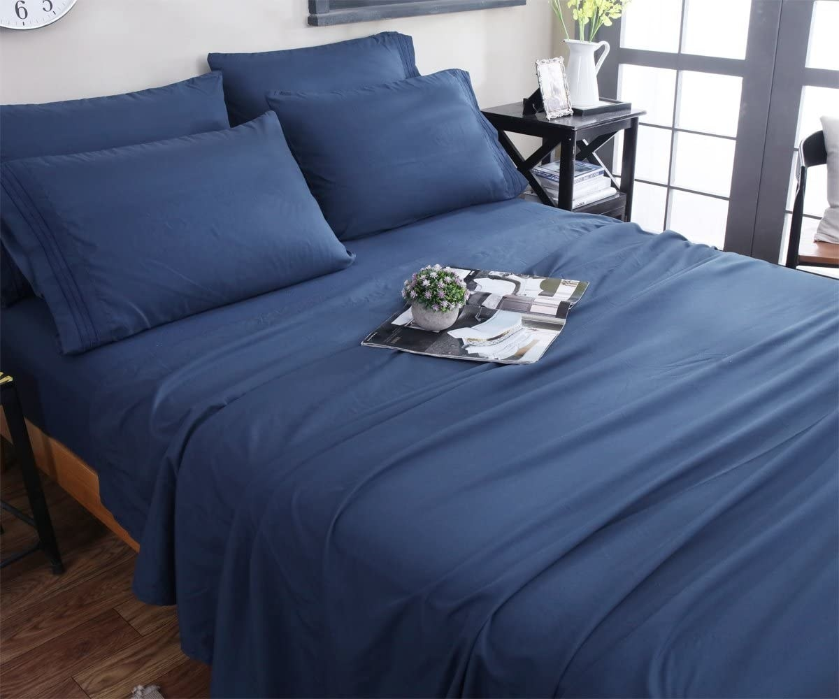 the sheets in navy blue on a bed