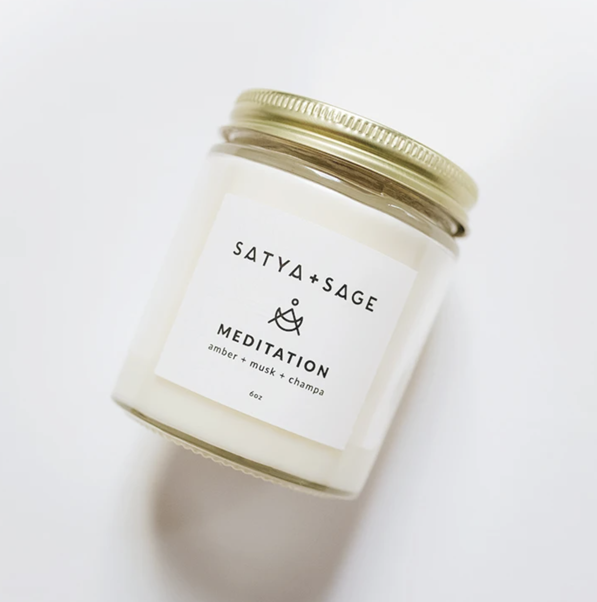 """A while candle that says """"Satya + Sage Meditation amber, musk, and champa"""""""