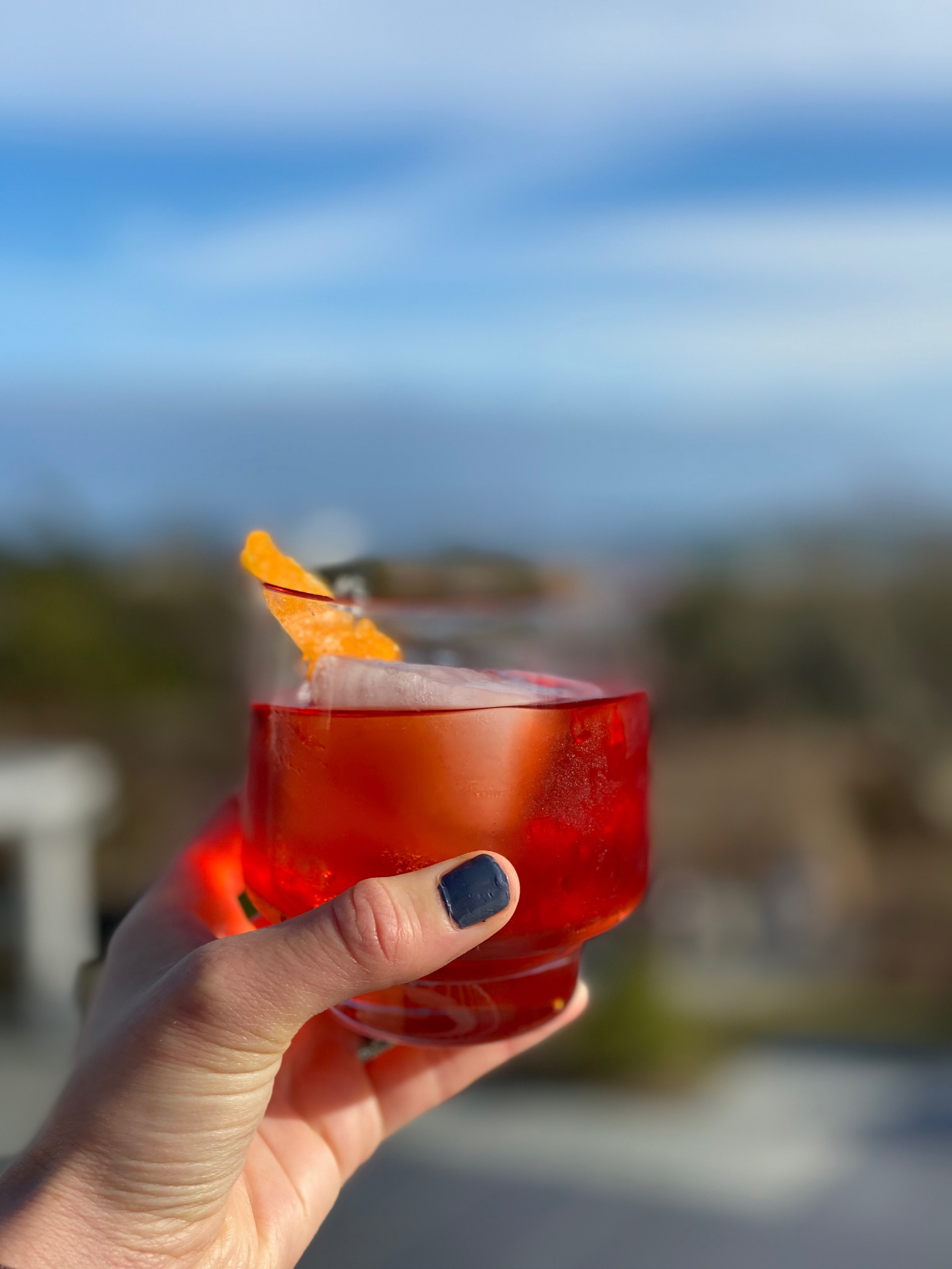 Holding a negroni outside with blue skies in the background.