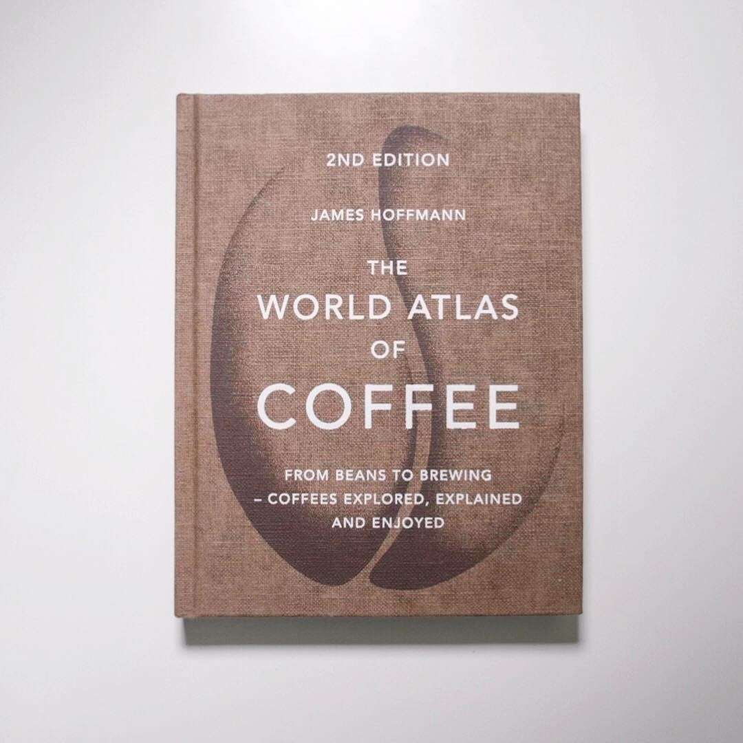 A large book called the world atlas of coffee on a plain background