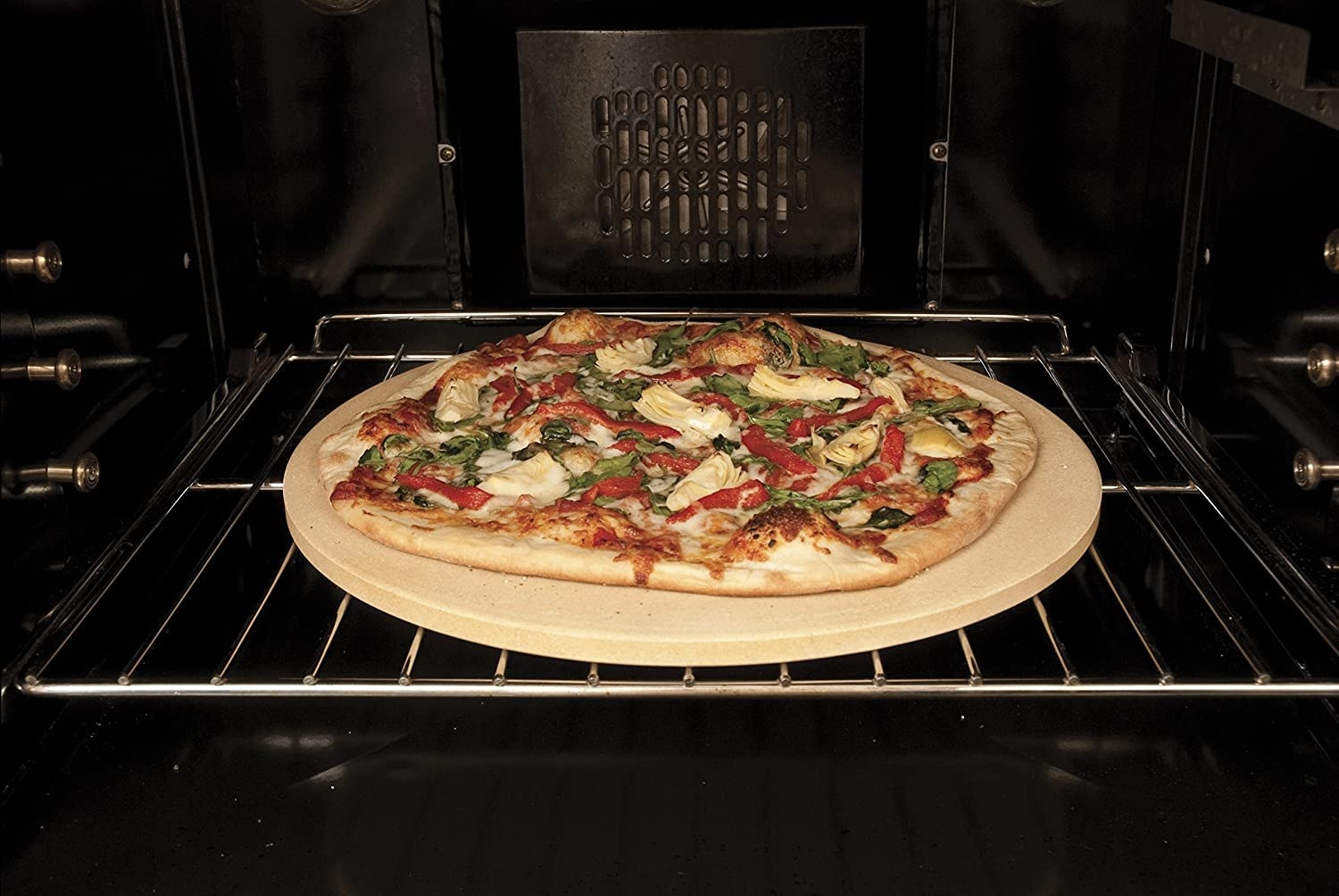 a pizza bakes on a pizza stone in oven