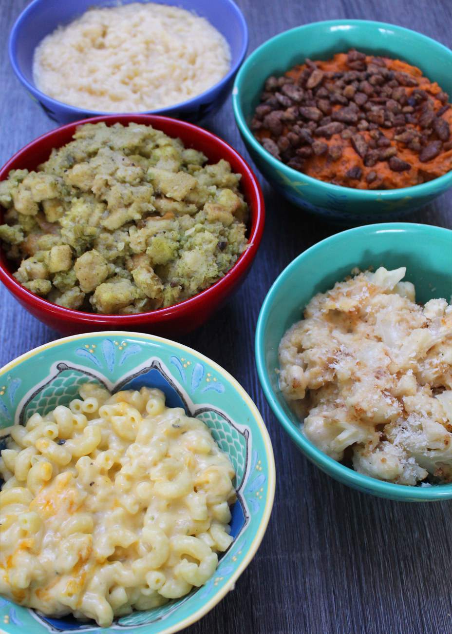Thanksgiving side dishes like mac 'n' cheese, scalloped potatoes, stuffing, mashed sweet potato, and regular mashed potatoes in bowls.