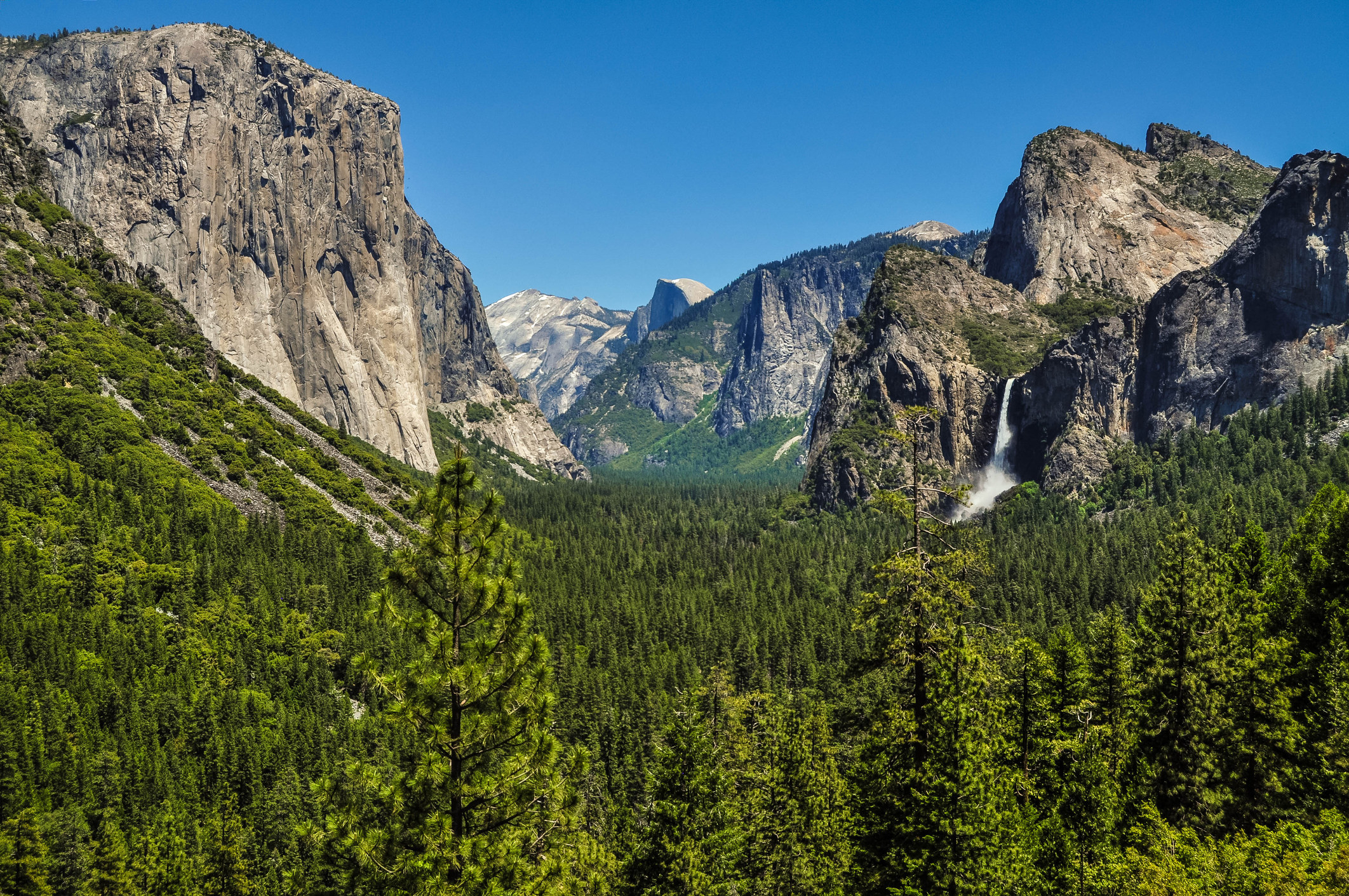 Yosemite's mountain range and forest floor with a waterfall in the background and a blue sky above.