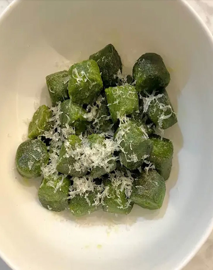 A plate of kale gnocchi with grated Parmesan.