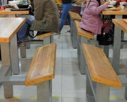 Tables in a mall food court with angled benches