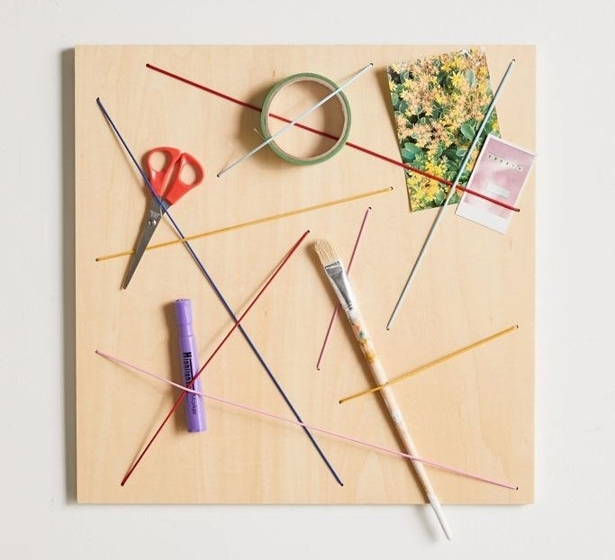 A wood board with colorful cords strung across with pictures, scissors, and other office supplies being held up
