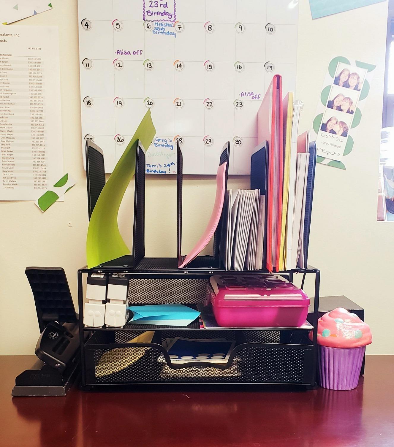 A reviewer's organizer with an assortment of desk supplies inside