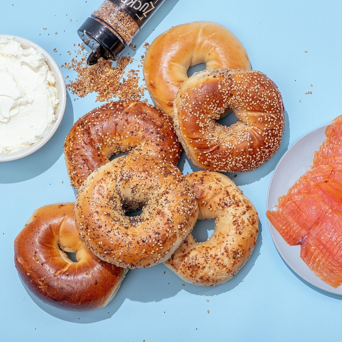six bagels next to seasoning, lox, and cream cheese