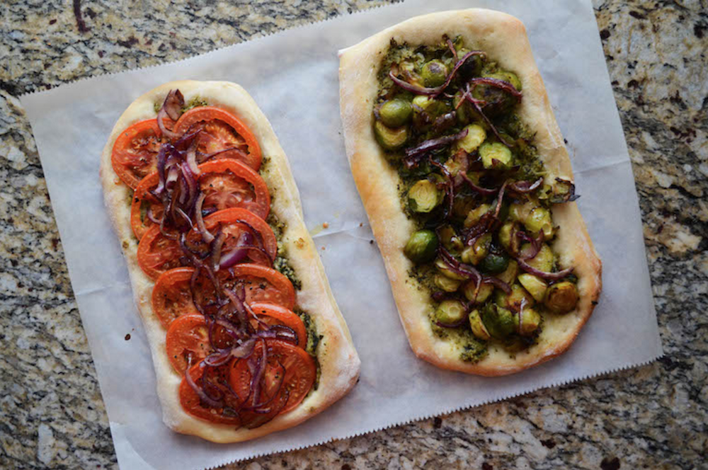 Two flat breads, one topped with sliced tomatoes, red onion, and pesto and the other with caramelized onion, Brussels sprouts, and pesto.