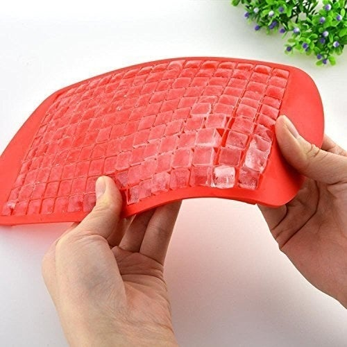 Small ice cubes being removed from a red silicone ice cube tray