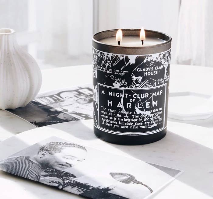 A two-wick candle with a drawn map of Harlem