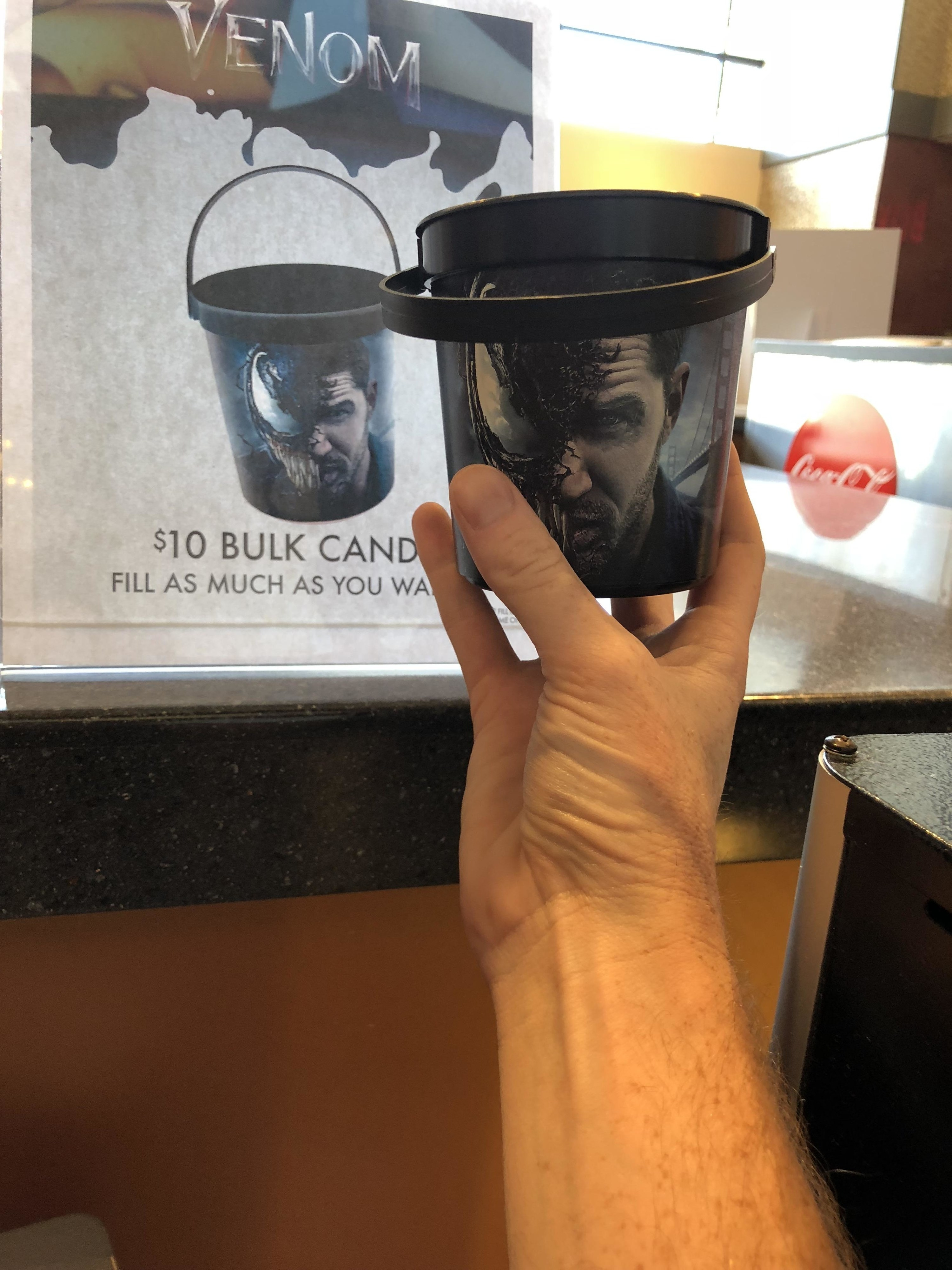 "A hand holding up a small bucket in front of an advertisement for the same bucket that reads ""$10 bulk candy fill as much as you want"""