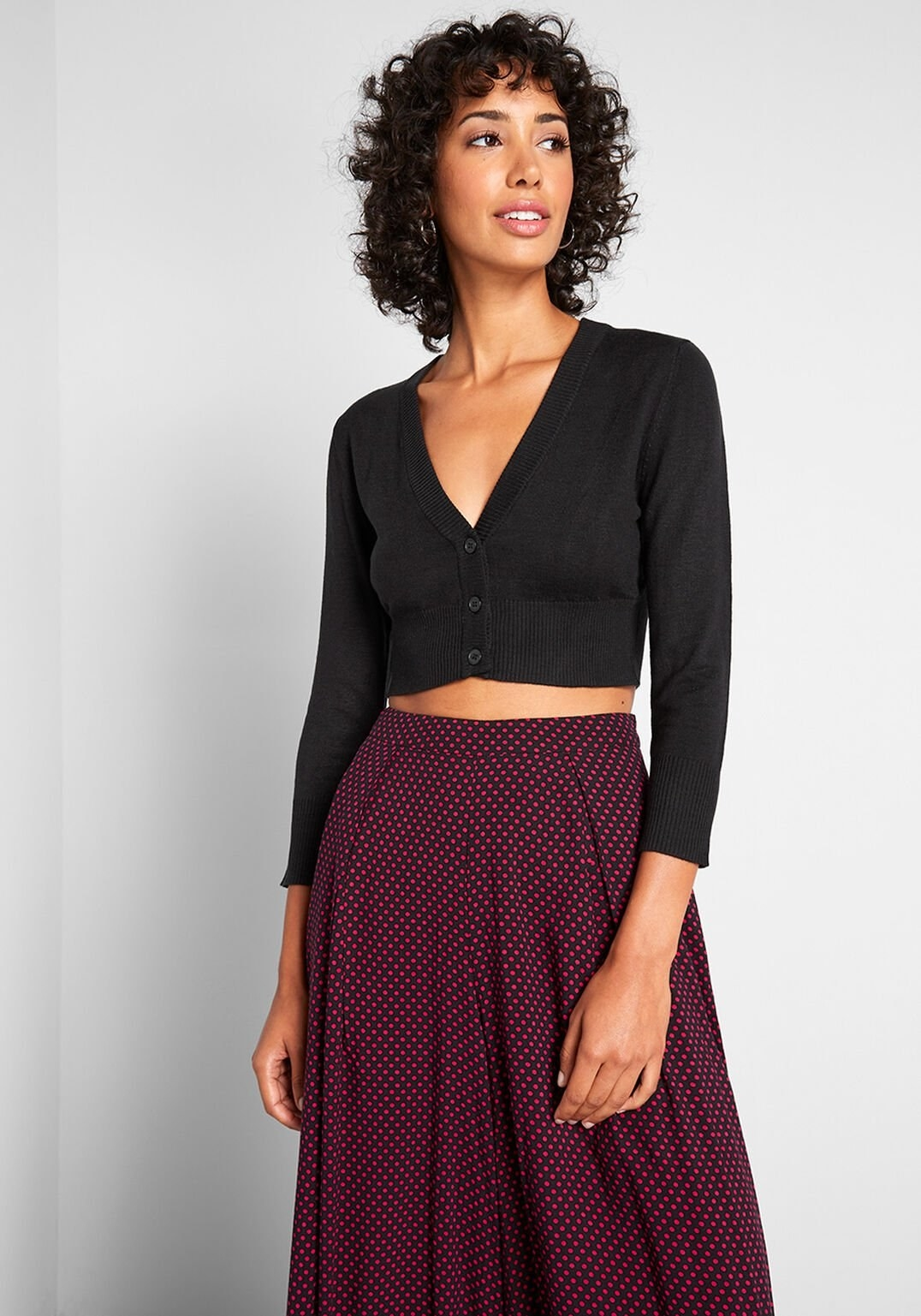 a model wearing the cropped cardigan in black with all three middle buttons closed