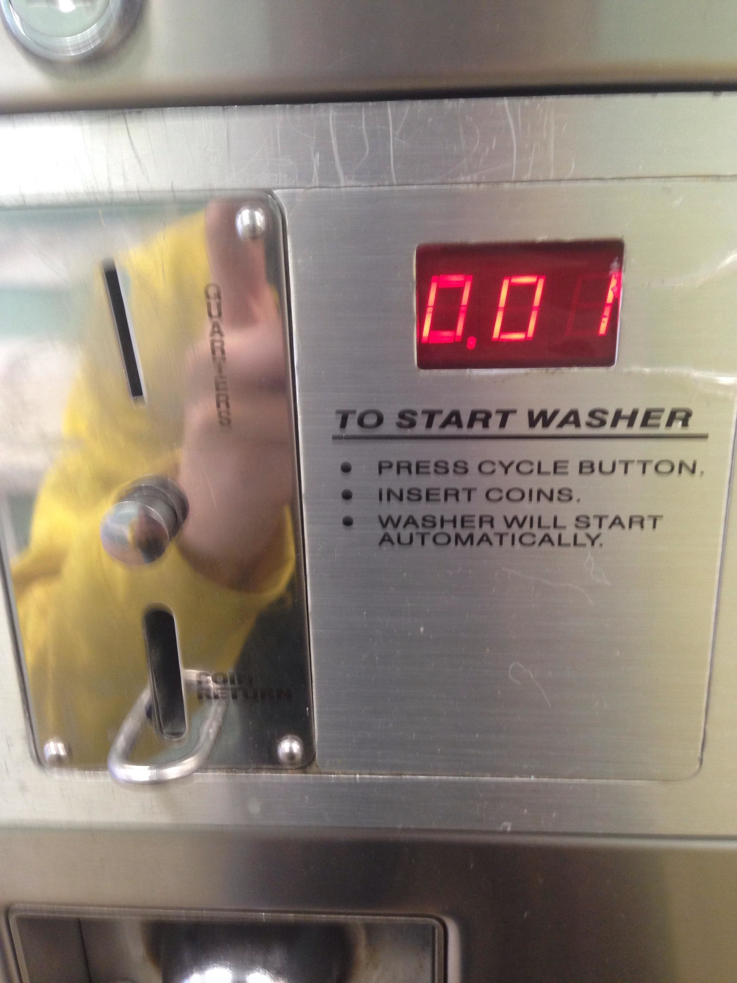 The coin slot on a washing machine that takes quarters with a digital display that reads 0.01