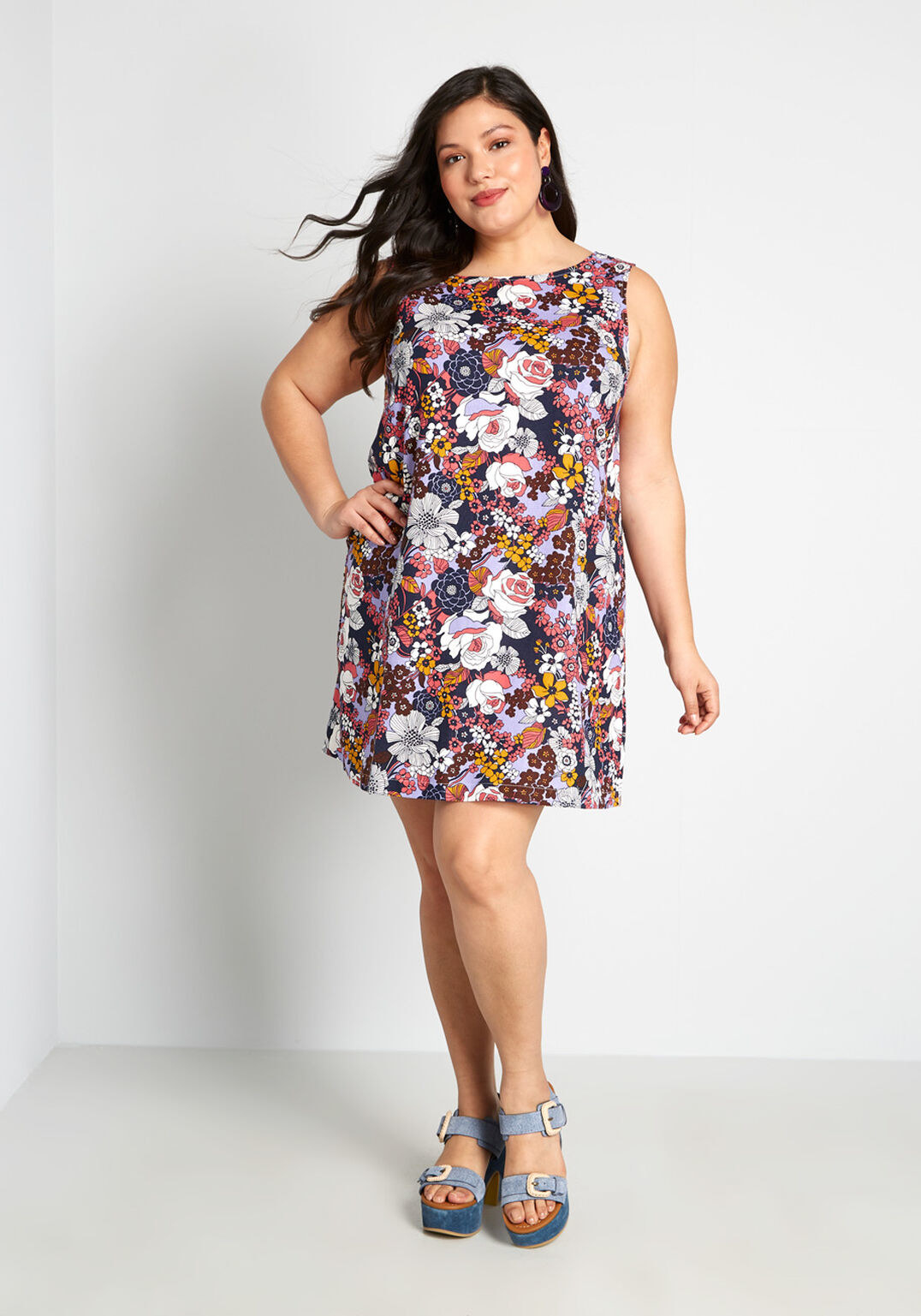 a model wearing the shift dress that is covered in an array of hand drawn blue, purple, white, burgundy, and yellow flowers